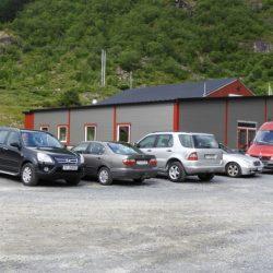 Flere biler parkert utenfor butikkbygget